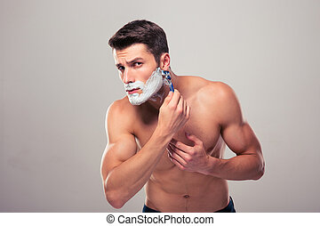 Young muscular man shaving