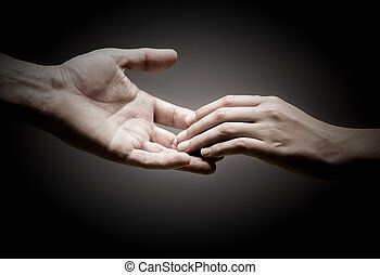 Solidarity - two hands are touching each other over black...