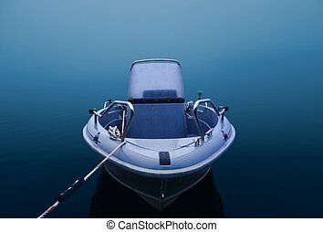 Motorboat in blue and thick fog
