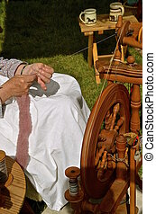 Wool spinning into yarn - A lady allows wool to slide...