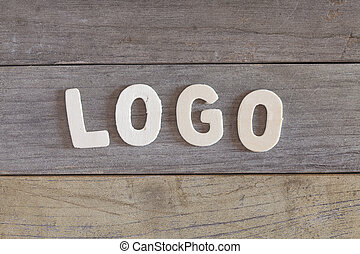 Logo - Word logo written with wood letters over a wooden...