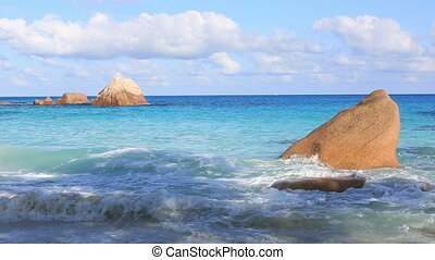 Waves breaking on granite boulders in beach of Anse Lazio....