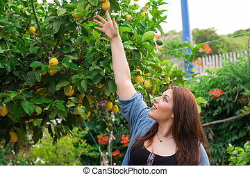 Girl trying to reach a juicy lemon