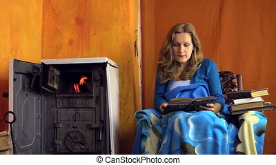 woman read book - Woman read book at home near warming stove...