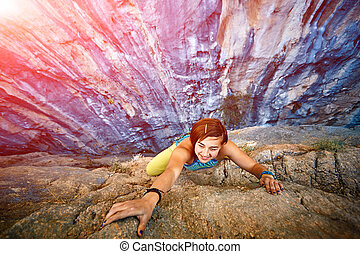 Rock climber climbing up a cliff - female rock climber...
