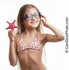 portrait of smiling girl in sunglasses posing with starfish