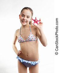 happy girl in swimming suit showing red starfish