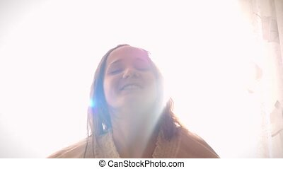 Slowmotion of young smiling woman is cheering a new day, dancing, stretching and smiling on the background of sunlight in the morning.