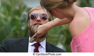 girl assistant brushes guitarists beard and corrects tie -...