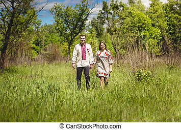 couple in traditional slavic clothes walking at meadow -...