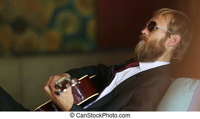 bearded man in black plays guitar sitting on sofa - bearded...