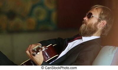 bearded man in black plays guitar sitting on sofa