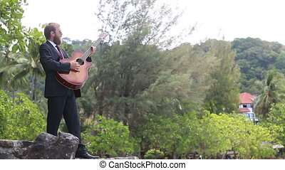 guitarist plays and gesticulates against tropical trees -...