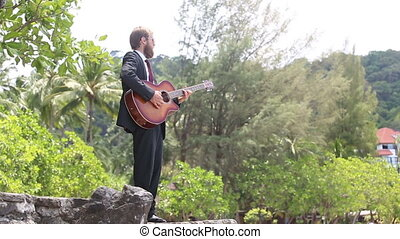 guitarist gesticulates against tropical trees - guitarist in...