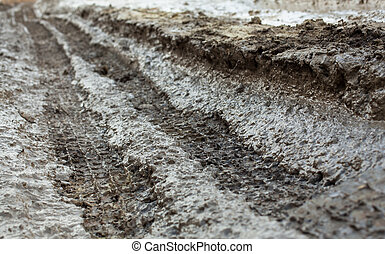 Wheel tracks on the muddy dirt road after the rain.