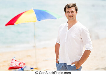 Portrait of handsome man in white short posing on beach at...
