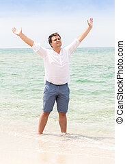 man standing with raised hands on beach and looking in the sky