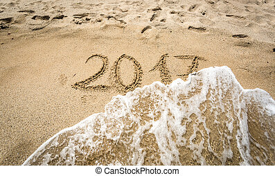 Closeup of 2017 written on sand being washed off by wave -...