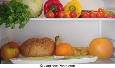 Opening the refrigerator door, a female hand puts all food from refrigerator and close The door before clean it
