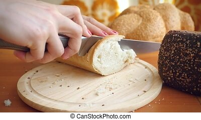 Slowmotion of Female hands cut French bread knife on a...