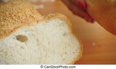 Variety of bread on the table in kitchen and woman hands put...