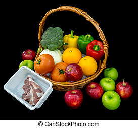 Composition with vegetables and fruits in wicker basket with pork isolated on black