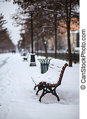 Bench, covered with snow, the city