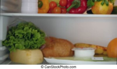 Woman inspecting refrigerator shelves indoors and she marks...