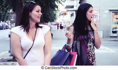 women walk in city shopping - Happy women walk and talk on...