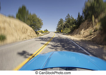 Car driving fast on open mountainous road with bends and...