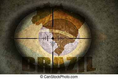 sniper scope aimed at the vintage brazilian flag and map