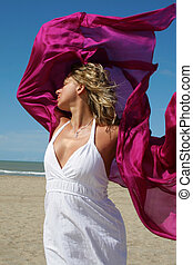 young women in white on beach with red fluttering scarf -...
