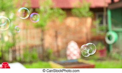 Soap bubbles - Young man blowing colorful soap bubbles