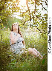 Pregnant sitting on the grass - A young pregnant woman...