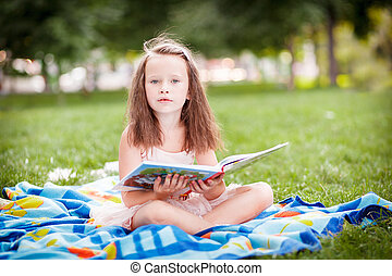 little girl in the park with a book - Young family relaxing...