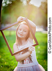 Girl and photoframe - Young family relaxing in the park...