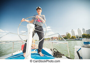 girl captain of the yacht - Young beautiful girl in the form...
