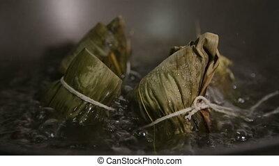 Zongzi boiling in a wok. Zhongzi is a traditional Chinese...