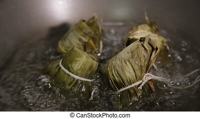 Zongzi boiling in a wok Zhongzi is a traditional Chinese...
