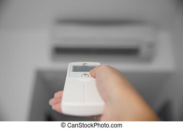A hand using a remote to activating air conditioning machine...