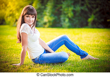 girl jeans sitting on the grass - Young beautiful brunette...