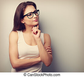 Thinking serious young woman in glasses looking Vintage...