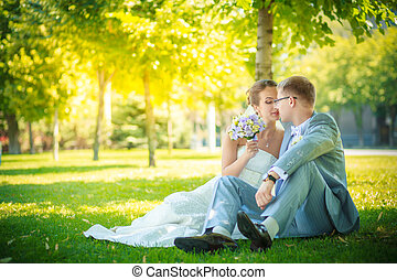 Bride and groom sitting on the lawn - The wedding ceremony...