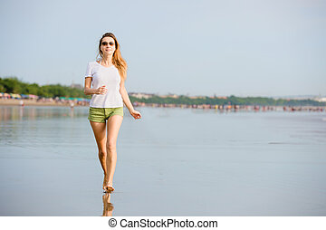 Young caucasion woman running on the beach at sunset enjoing...