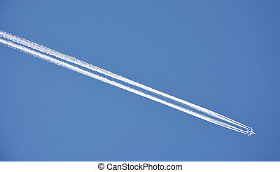 Condensation trace left from a 4-engine airplane on blue sky