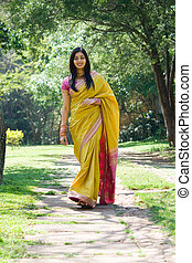 inidan woman walking - an indian woman walking in the park...