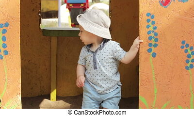 Child in toy house - Boy child in painted wooden house