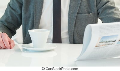 Businessman drinking coffee and reading newspaper - Breaking...