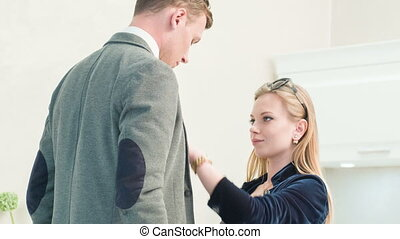 Woman fixing tie of handsome man - : Getting him ready...