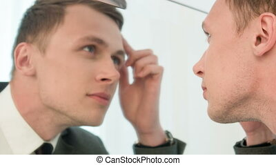 Young man fixing his hair in front of mirror